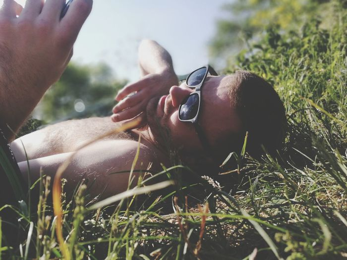 Young man using phone while lying on grassy field
