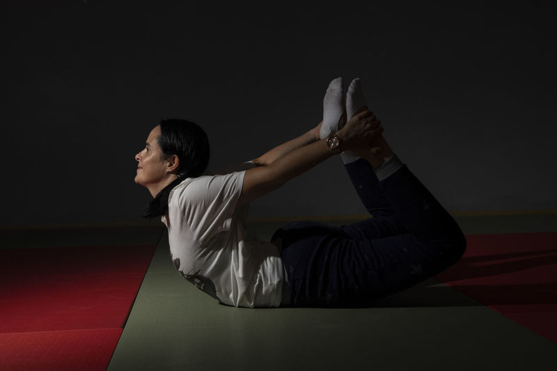 Portugal; Aula de Yoga Yogagirl Yoga Poses One Person Young Adult Indoors  Leisure Activity Sport Real People Lifestyles Arts Culture And Entertainment Studio Shot Side View Three Quarter Length Skill  Full Length Relaxation Concentration Adult Casual Clothing Looking Away Black Background Hairstyle Contemplation Profile View