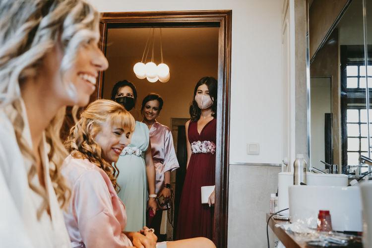 Bride and bridesmaid preparing for wedding ceremony