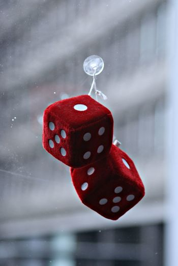 Close-up of red dice hanging on window glass
