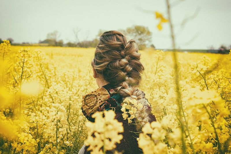 Woman Standing Amidst Yellow Crops On Field