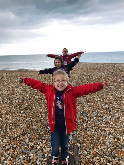 Sisters arms outstretched standing in row at beach