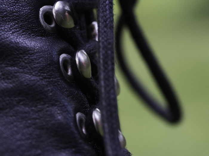 Close-up of black shoe against green background