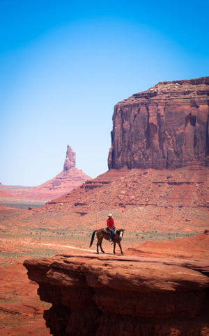 Cowboy at Monument Valley Adult Adventure Beauty In Nature Blue Canyon Clear Sky Cowboy Day Desert Full Length Horse Landscape Monument Valley Nature Outdoors People Rock - Object Rock Formation Sky Travel