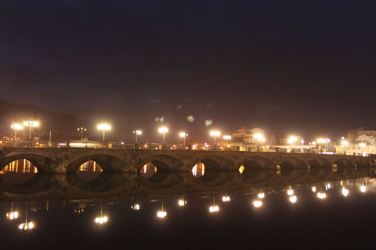 Illuminated Burgo Bridge Over Lerez River Against Sky At Night