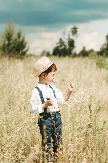 Rear view of boy with arms raised on field