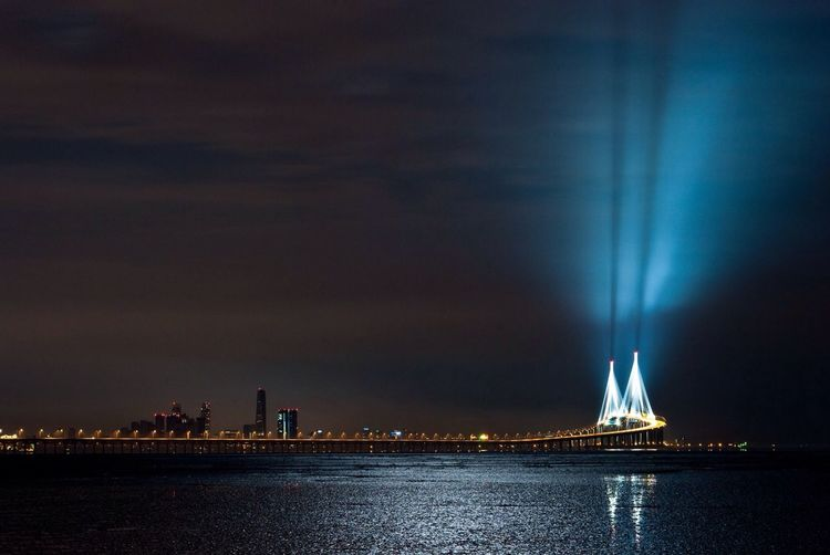 Illuminated cross sea bridge and cityscape with peaceful waterfront