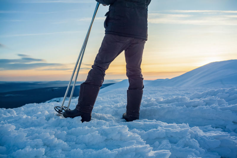 Low section of man standing on snow covered landscape during sunset