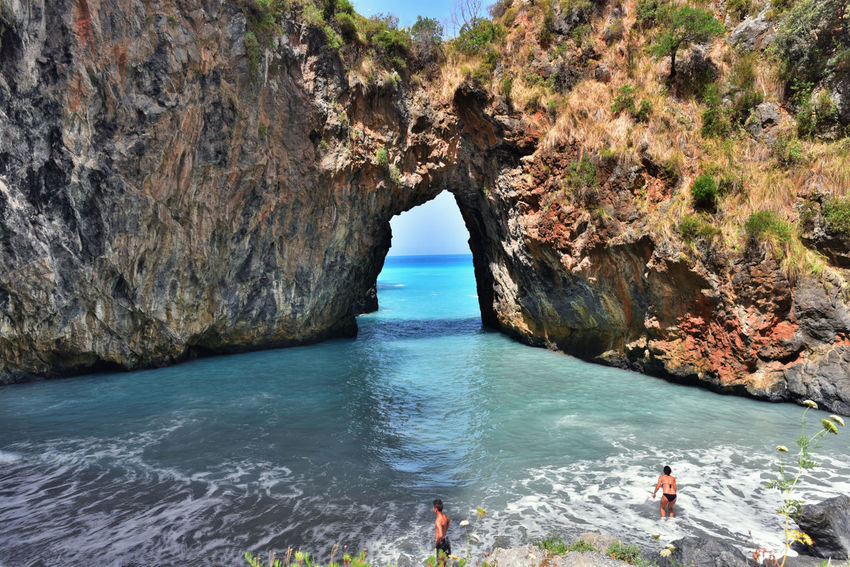 Natural Arch Azzuro Travel Clear Sky Sunlight Beauty In Nature Cliff Tranquility Arco Magno Calabria (Italy) Horizon Over Water Vacations Sea Wave Mountain Sky Beach Real People Rock - Object Rock Formation
