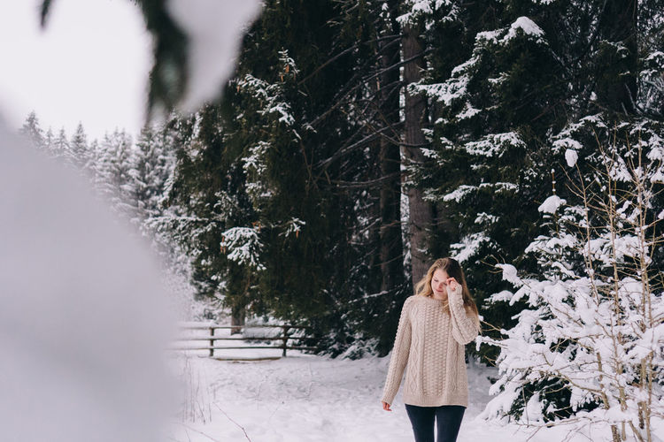 Woman standing on snow covered trees