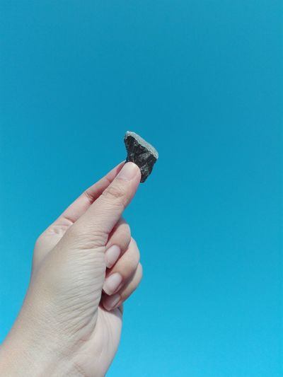 Cropped Image Of Hand Holding Stone Against Clear Blue Sky