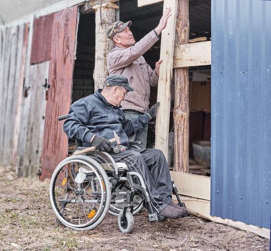 Man sitting on wood outside house