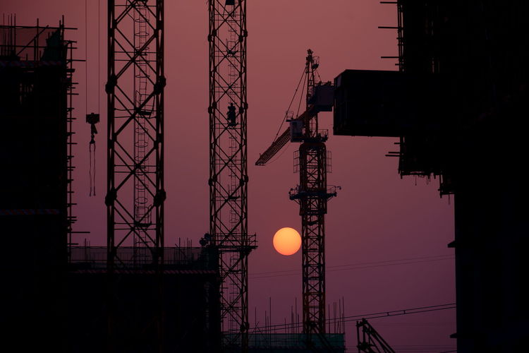 workers in the sunset standing on the crane