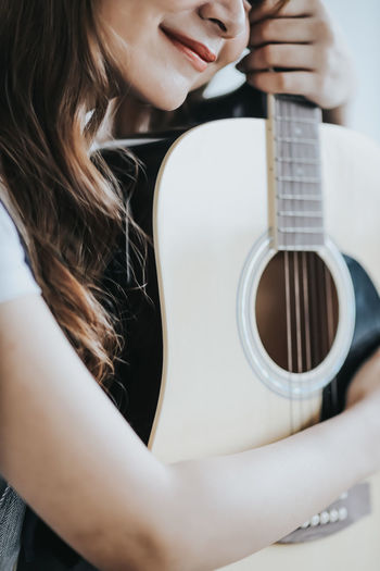 Midsection of woman holding guitar