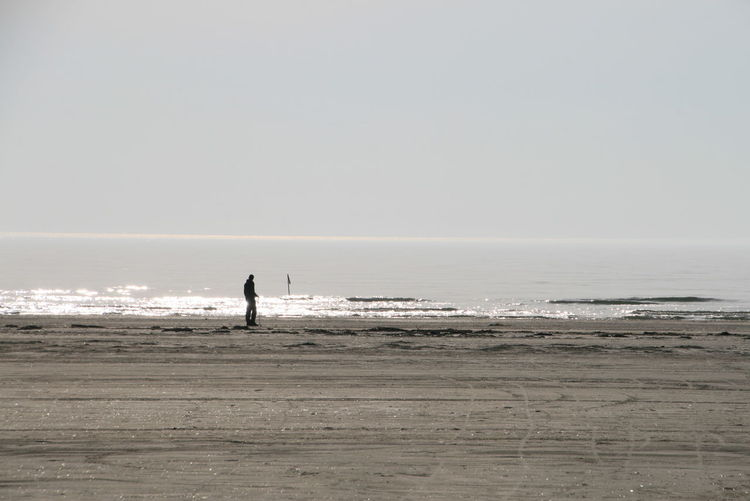 Silhouette man standing at beach against clear sky