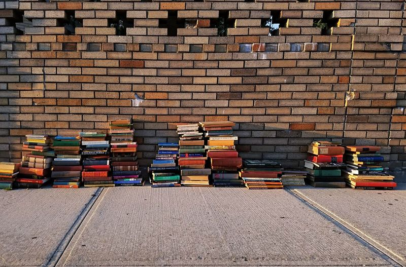 Stack Of Books On Footpath Against Brick Wall