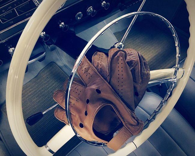 Leather gloves on steering wheel of vintage car