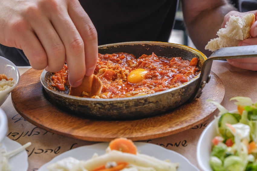 Breakfast Egg Yolk Frying Pan Middle East Shakshouka Tomato Sauce Close-up Food Freshness Healthy Eating Holding Human Body Part Human Hand Indoors  Lifestyles One Person Ready-to-eat Real People Reastaurant Savory Food Selective Focus Serving Size Spice Table Wellbeing