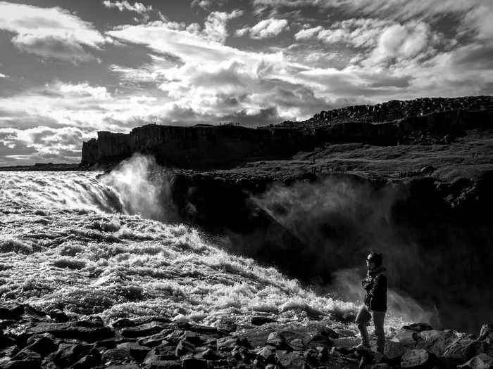 Man standing by dettifoss against cloudy sky