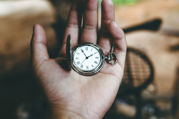 Close-up of hand holding pocket watch