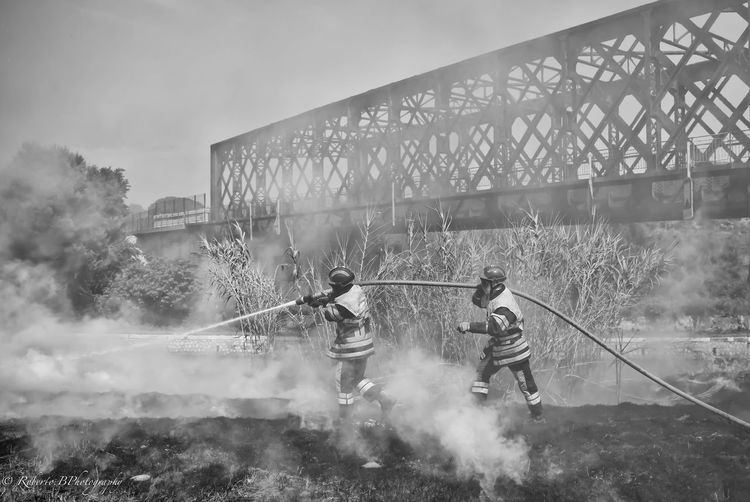 Firefighters at work by bridge against sky