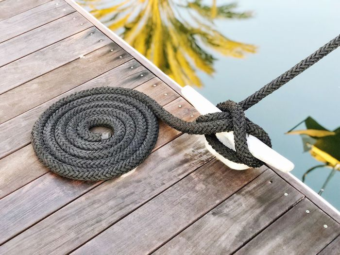 Close-up of rope tied on wooden pier