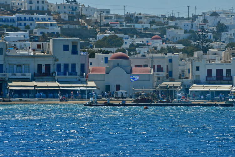 panoramic seaside view of Mykonos with white buildings and a church with red dome Building Exterior Built Structure Architecture Water Building City Waterfront Residential District Day Nature Outdoors Sea Cityscape House People Men Mykonos,Greece Chora Seaside Cityscape Church Greek Architecture Panoramic View Travel Destinations Tourism Summertime Tourists