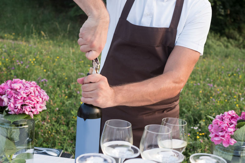 Midsection of man opening wine bottle while standing at yard