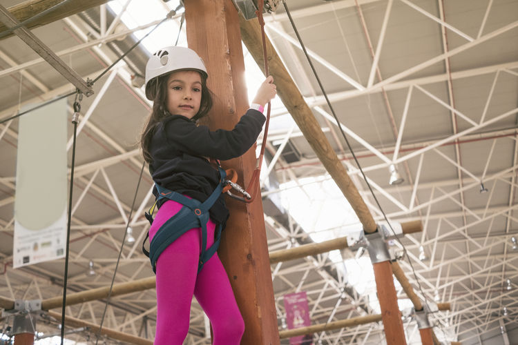 Low angle view of girl hanging on ropes with safety harness