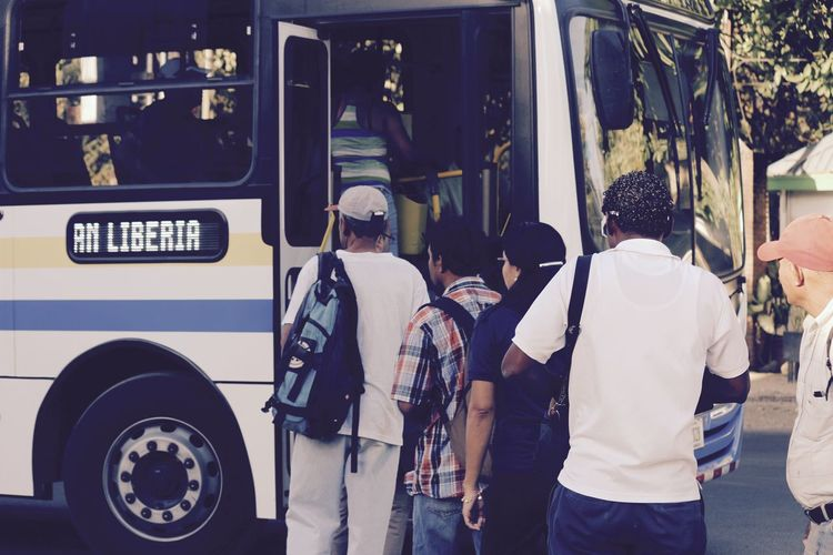 Rear View Of People Entering Into Bus
