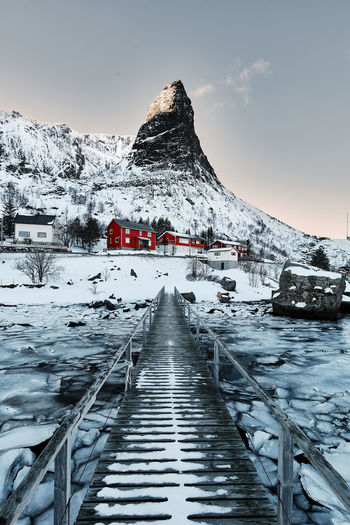 Footbridge over frozen lake against snowcapped mountains