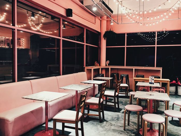 Empty chairs and tables in illuminated restaurant