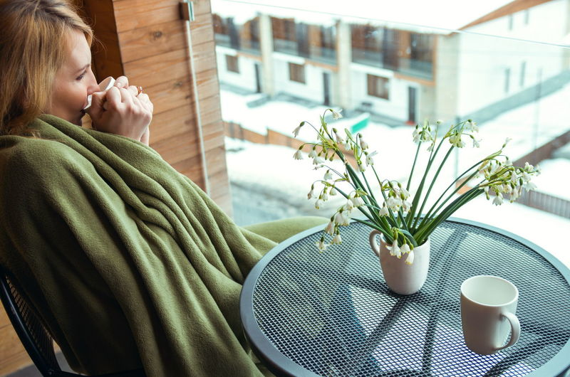 Midsection of woman with coffee cup on table at home