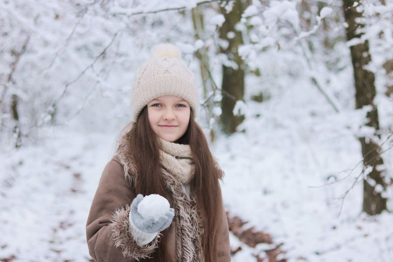 Portrait of a smiling girl in snow, holding a snowball in her hand