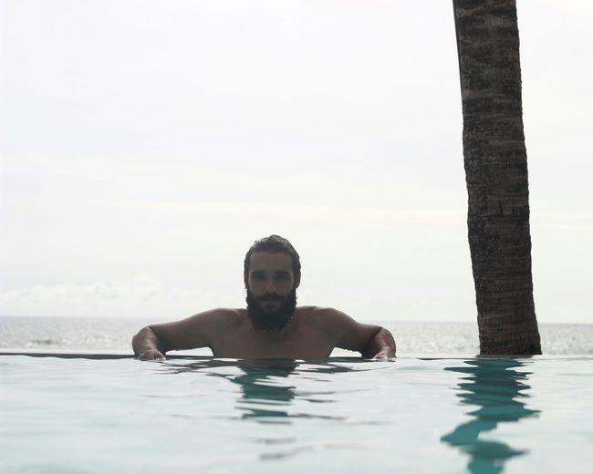 Portrait of man in infinity pool against sky
