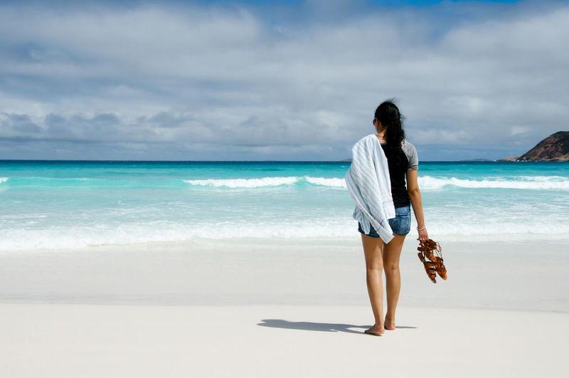 Rear View Of Mid Adult Woman Standing At Beach Against Cloudy Sky