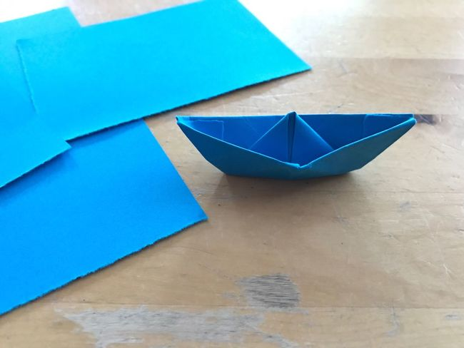 Paper Ship Paper Boat Boat Table Childhood Blue Sheet Piece Of Paper Pieces Blue Paper Selfmade Homemade Hobbies Make Crafting Handicraft Indoors  Close-up No People Day Handicraft Work Wood - Material Wood Table