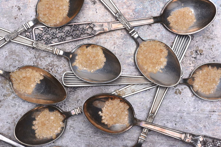 Silver spoonfuls with brown sugar on metal table top view Sugar Choice Close-up Cooking Pan Directly Above Eating Utensil Food Food And Drink Freshness Healthy Eating High Angle View Household Equipment Indoors  Kitchen Utensil No People Preparation  Serving Scoop Spoon Still Life Table Variation
