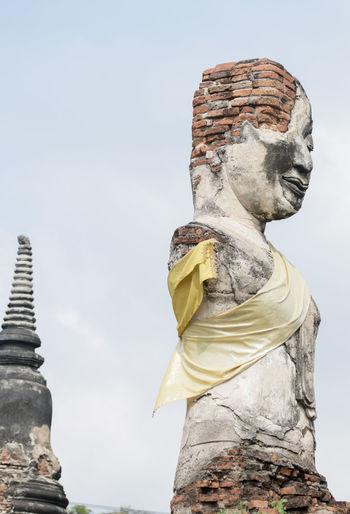 Low angle view of old damaged buddha statue and temple against sky