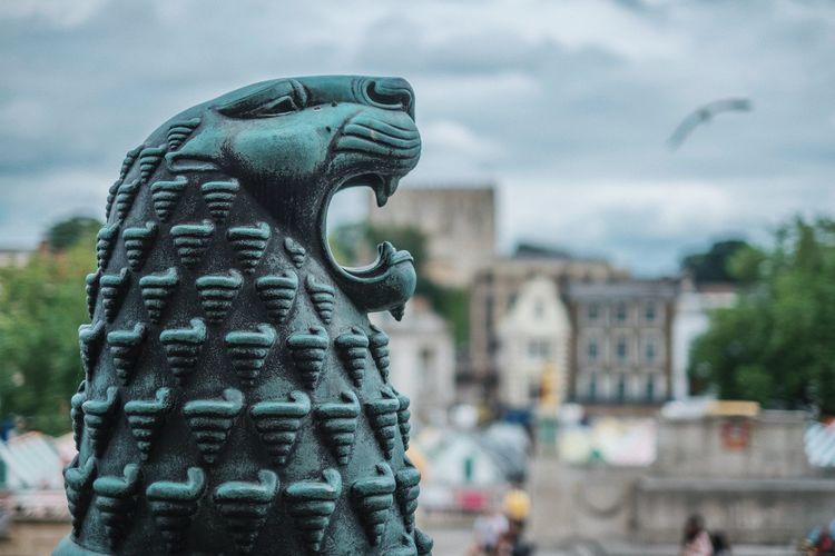 Gargoyle against buildings and sky in city