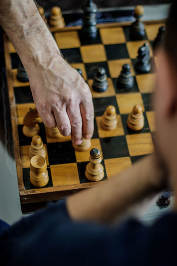Low angle view of man playing on chess board