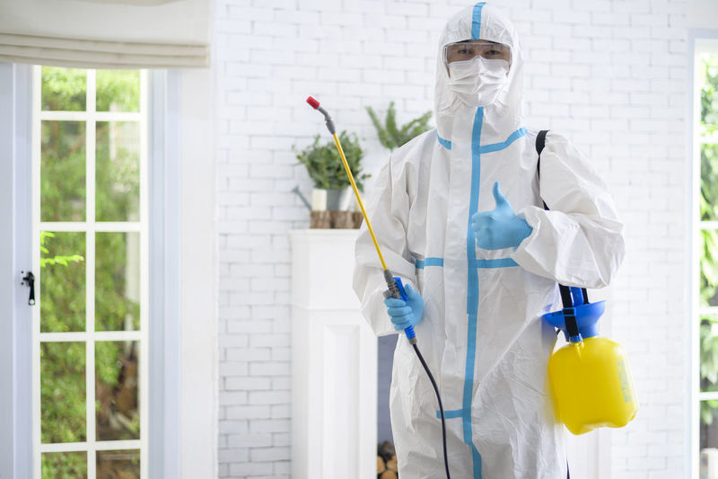 Portrait of man wearing protective suit standing at home