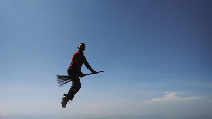 Low angle view of a man flying on broom against sky