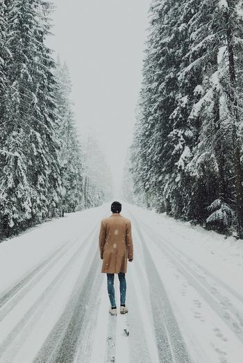 Rear view of man walking on snow covered road