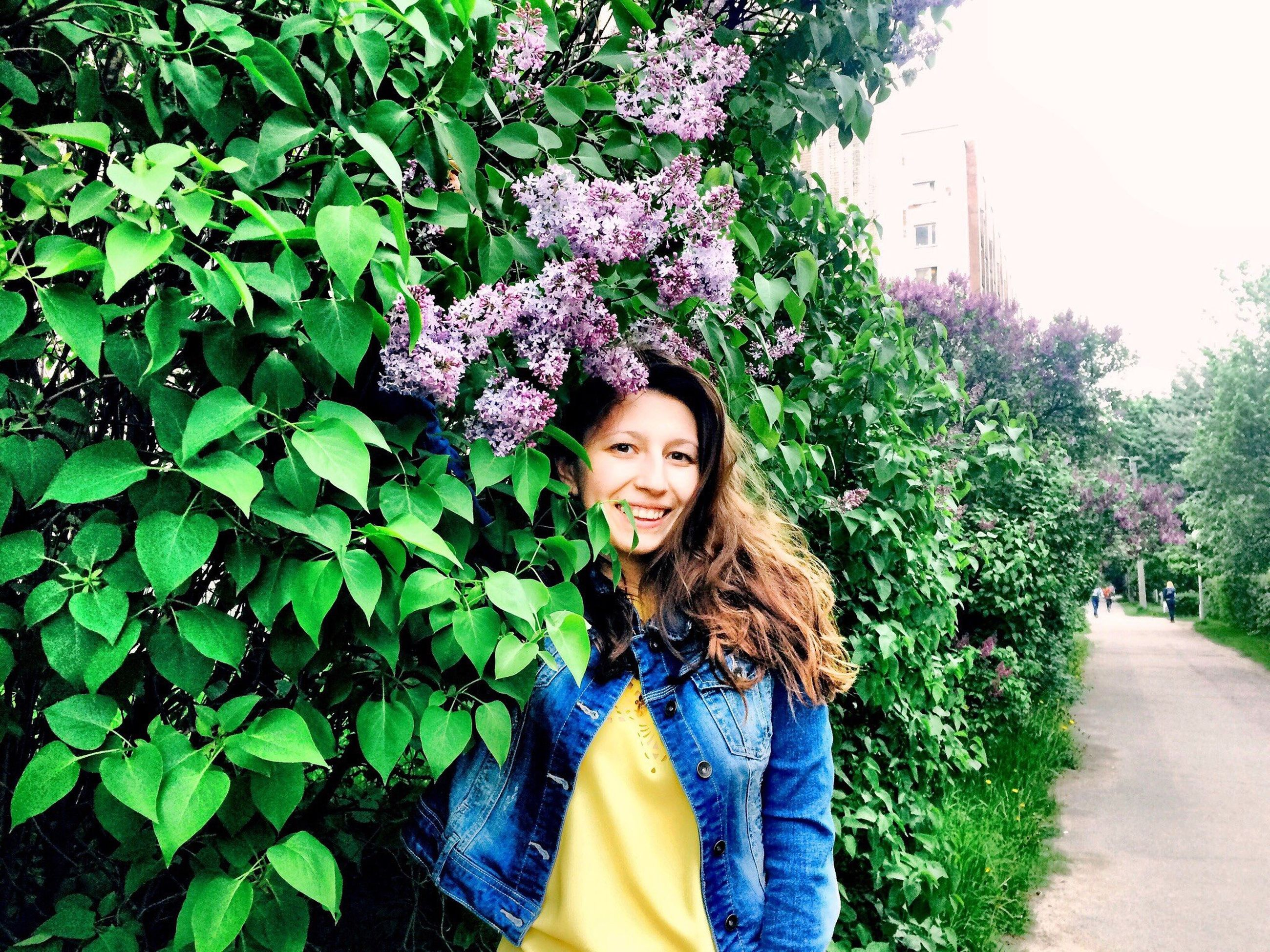 person, lifestyles, young women, young adult, leisure activity, looking at camera, casual clothing, tree, portrait, smiling, long hair, front view, growth, flower, standing, plant, park - man made space