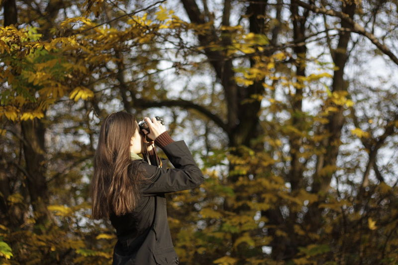 Side view of young woman photographing while standing against trees in forest
