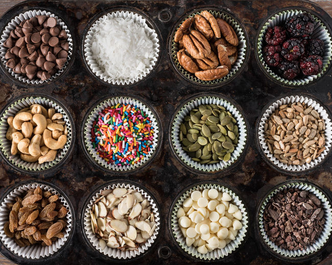 Baking ingredients Cashews Chocolate Coconut Country Ingredients Nuts Rustic Almonds Baking Candy Chips Close-up Directly Above Indulgence Milk Muffin Tin Pecans Pepitas Pumpkin Seeds Raisins Slivered Sprinkles Sunflower Seeds Top View Variation