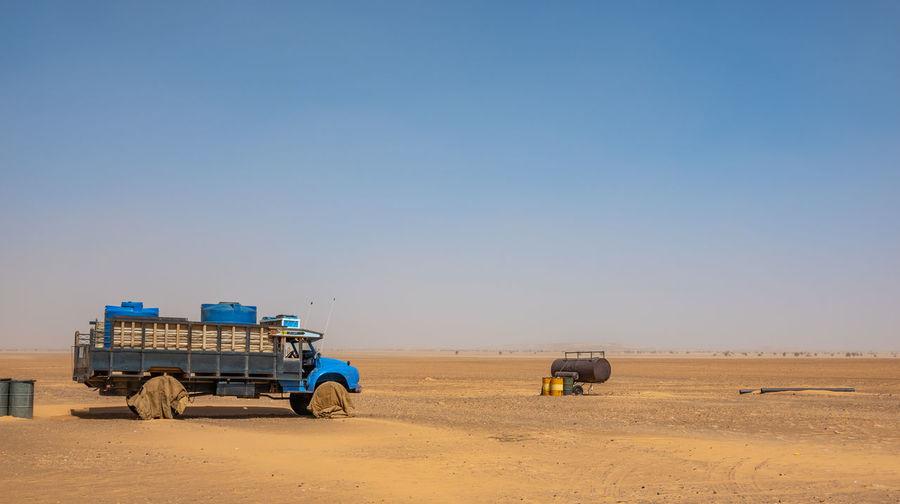 Lifeguard hut on desert against clear blue sky