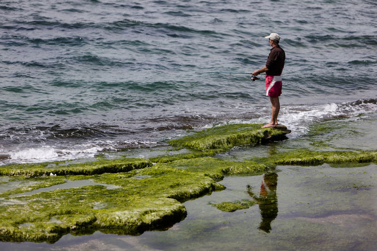 Mature man fishing while standing on moss covered rock by sea