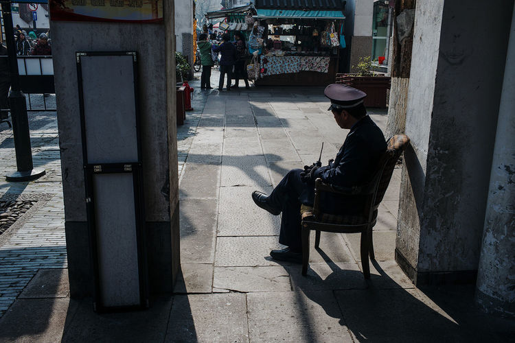 Security Guard Sitting On Chair Against Building Wall